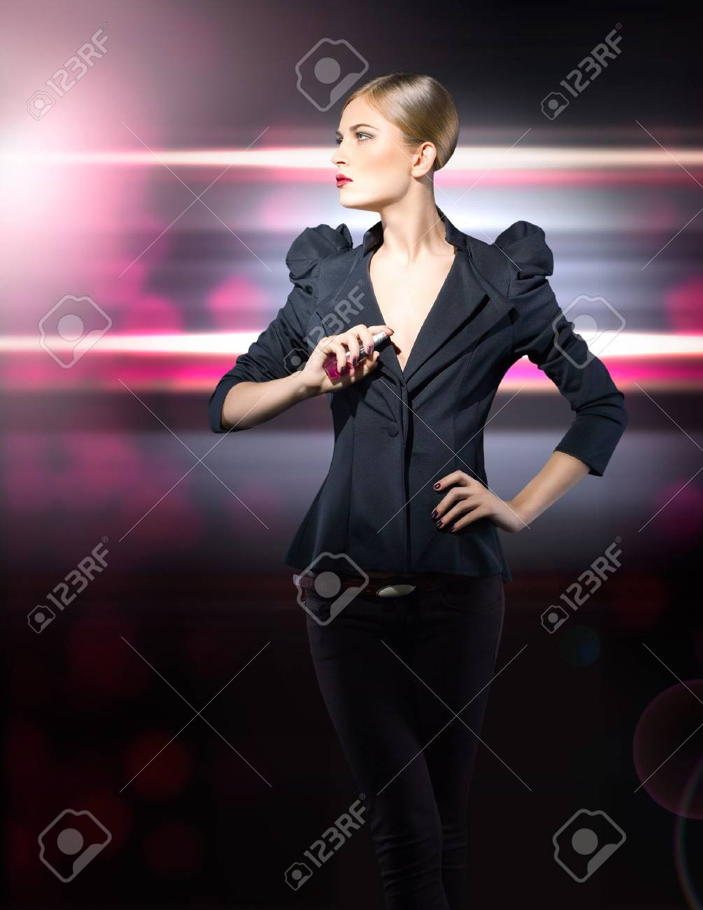 glamorous girl in a black jacket with a bottle of perfume in her Stock Photo - 12195715