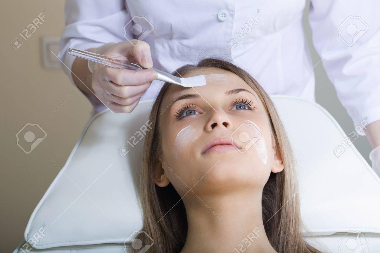 Beautiful woman with facial mask at beauty salon - 14715039