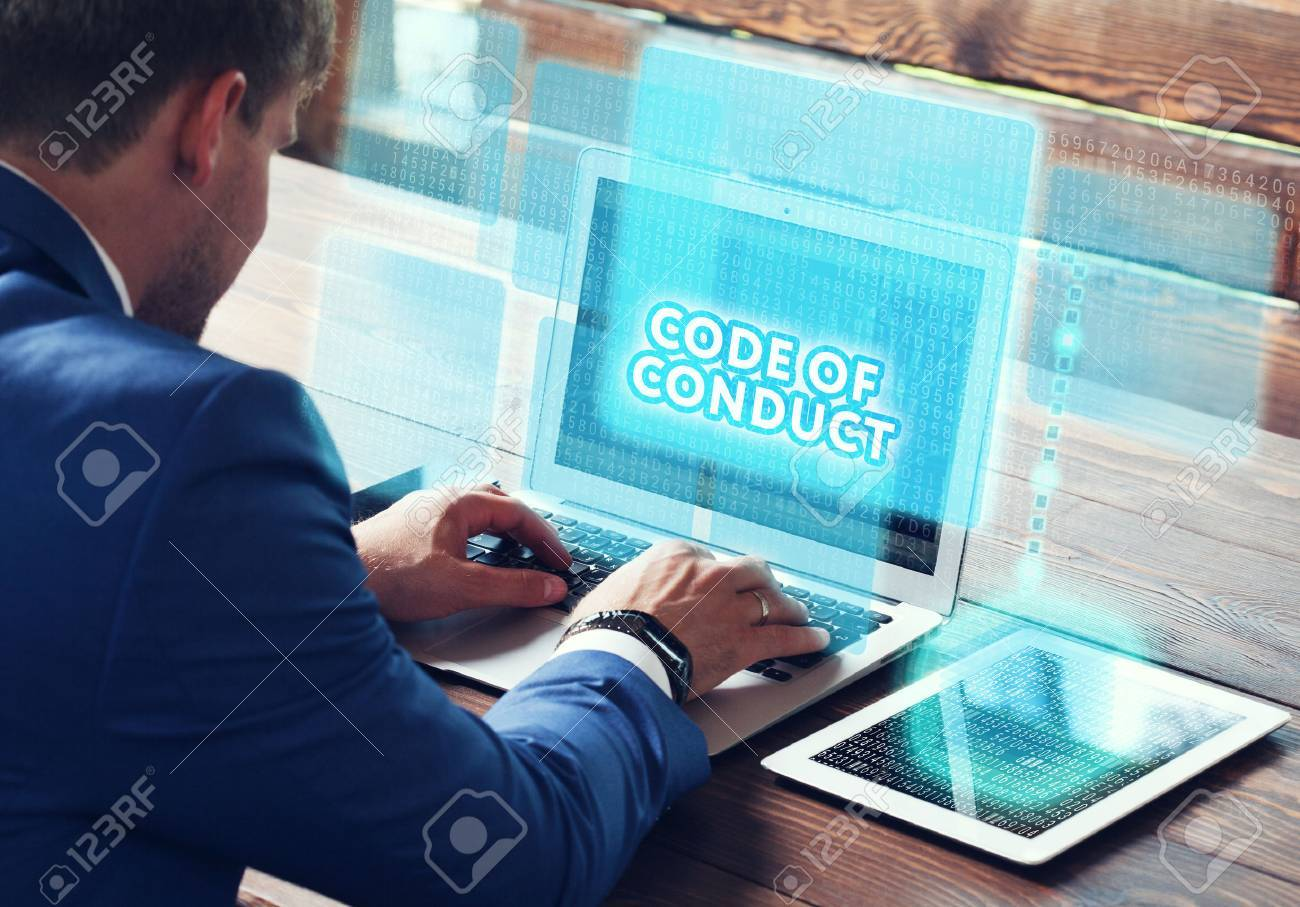 Business, technology, internet and networking concept. Young businessman working on his laptop in the office, select the icon Code of conduct on the virtual display. - 75575250