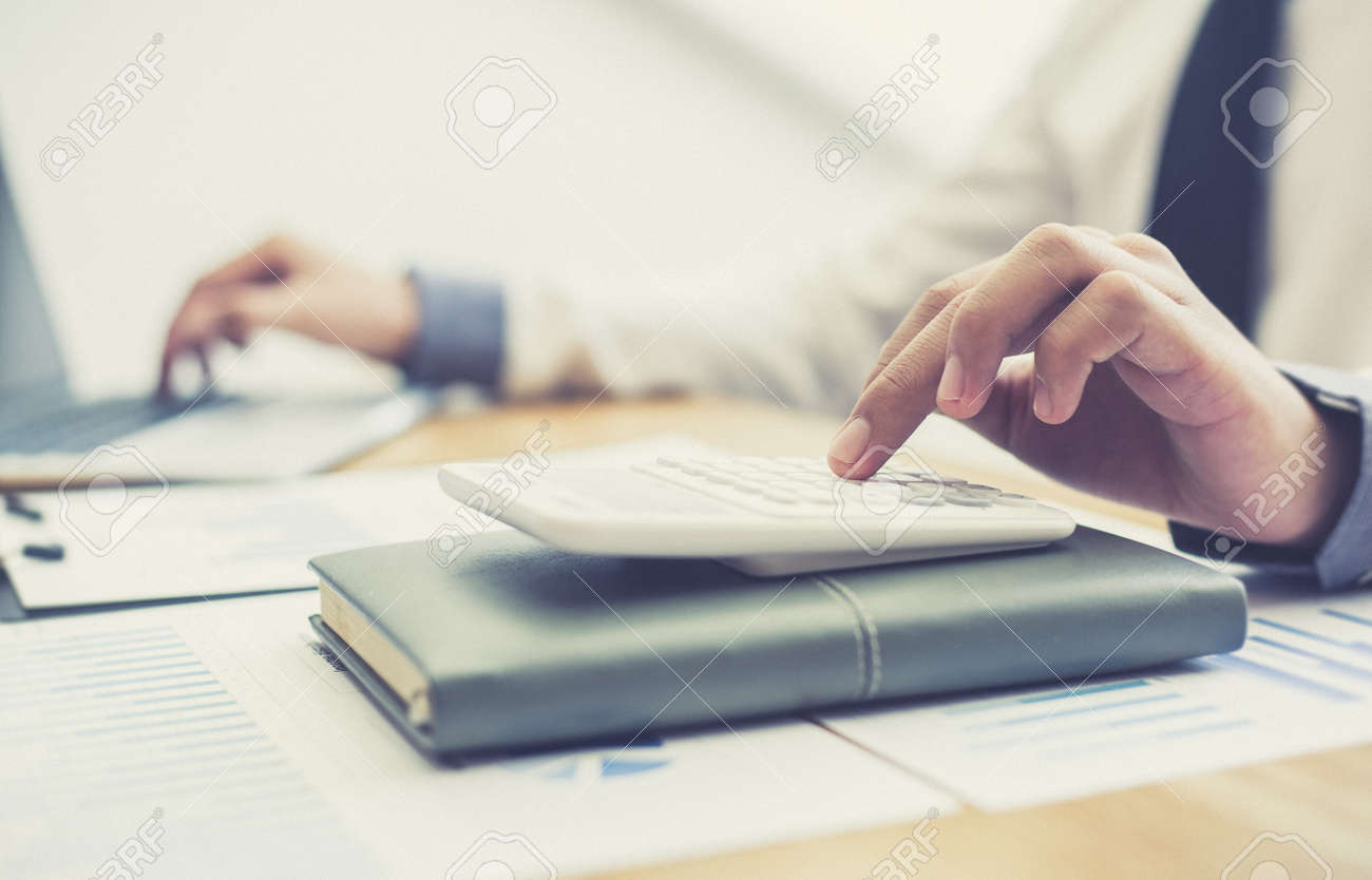 Business men use calculators to calculate the company's tax and revenue in the office, Financial and accounting banking concepts. - 142954068