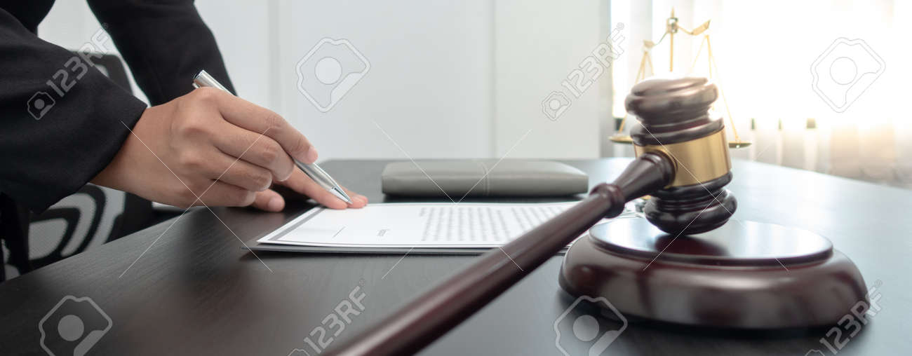 Judge or a lawyer works documents in the courtroom and analyze the various laws for justice and accuracy, Litigation and justice concept. - 157444288