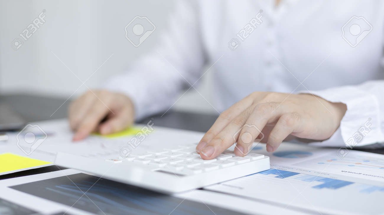 Young Asian businesswoman presses a calculator to calculate income tax and corporate income in a private office, Finance, Accounting, Tex, Statistical graphs of marketers investing in real estate. - 169218374