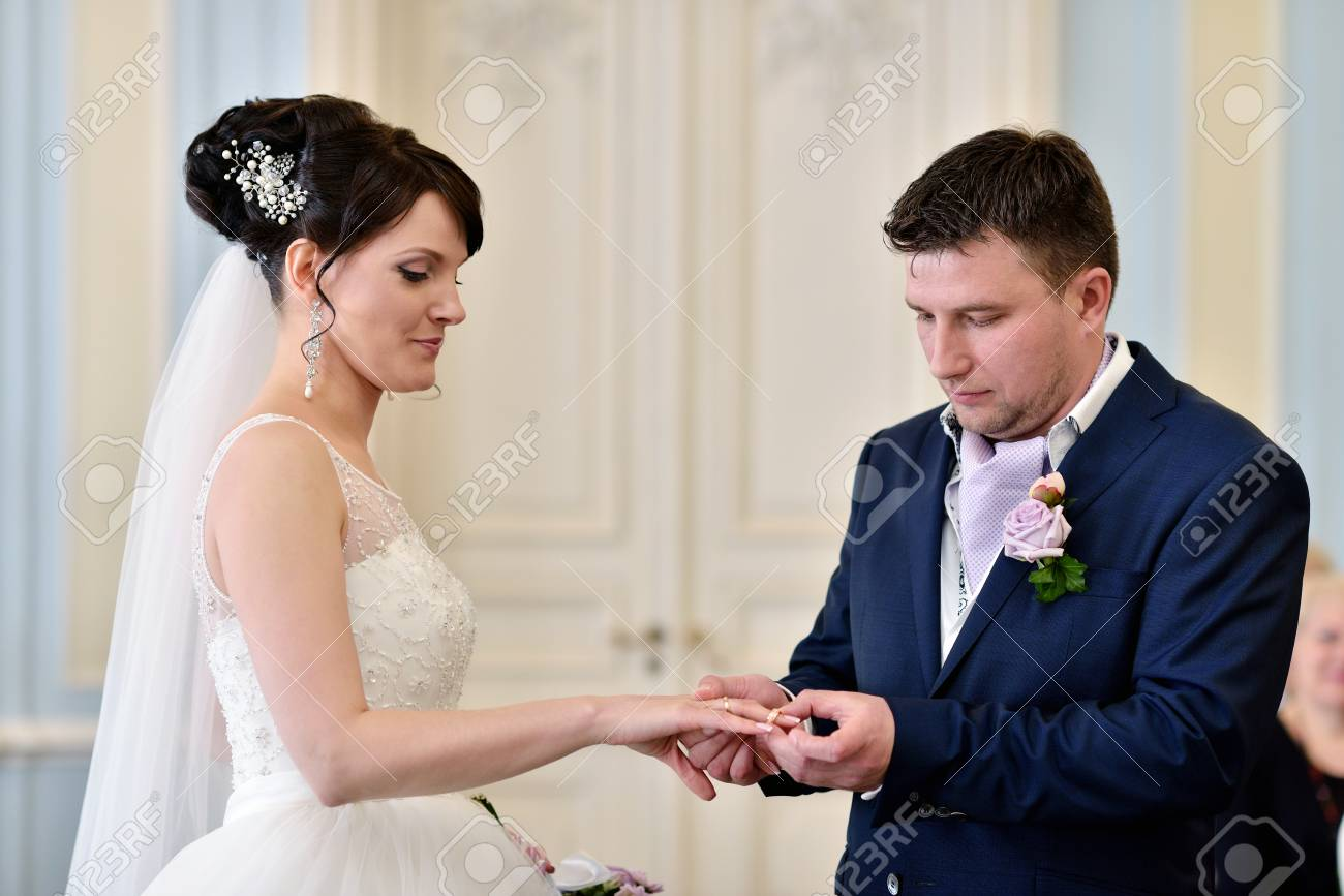 Beauty Bride And Handsome Groom Are Wearing Rings Each Other ...