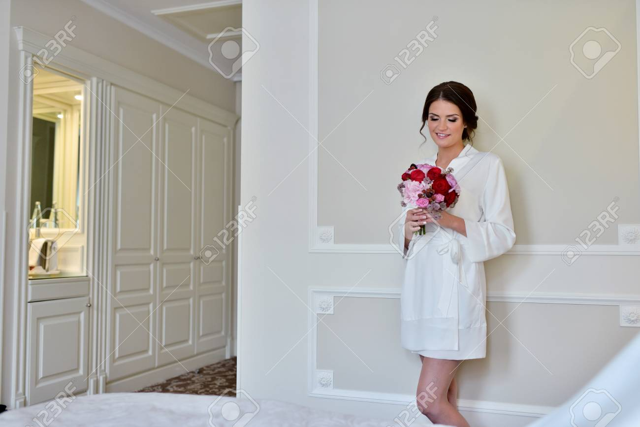 Beauty Bride In Dressing Gown With Bouquet Indoors. Beautiful ...