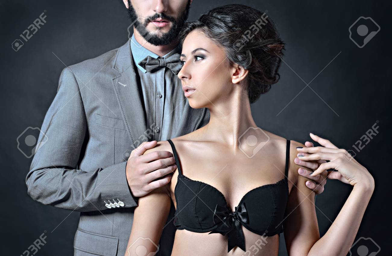 de2e40020f Beautiful lady in bra with handsome guy in suit. Young couple is hugging  each other. Portrait of girl in underwear and boy indoors in passionate pose .