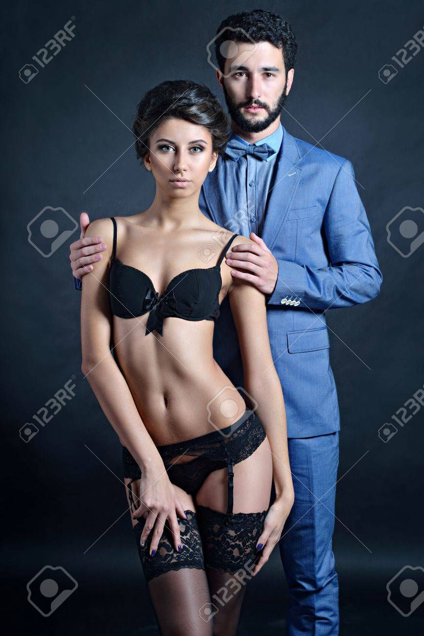 8a4866ffa6 Beautiful lady in panties and bra with guy in suit. Young couple is hugging  each other. Portrait of girl in underwear and boy indoors in passionate pose .