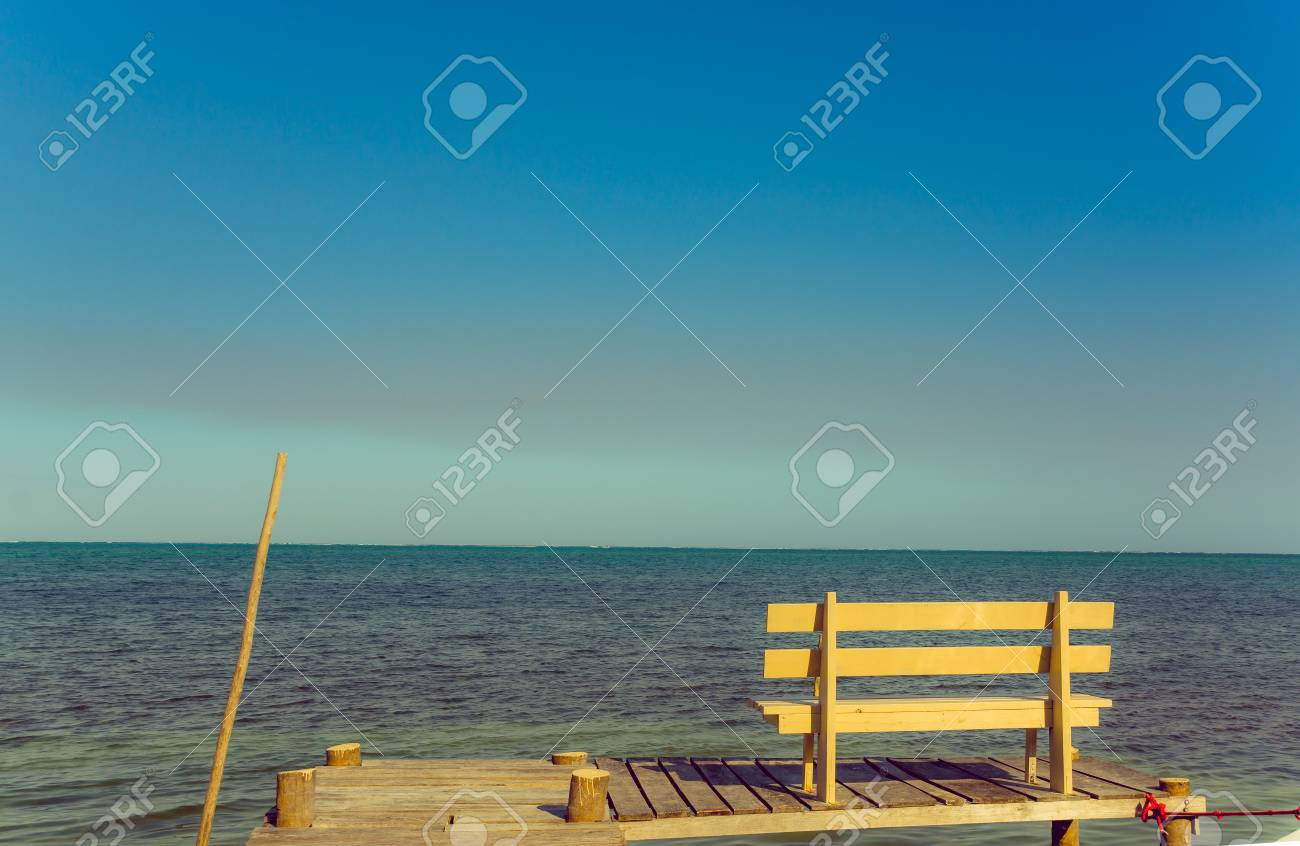 wooden bench over pier dock jetty with relaxing ocean view caye
