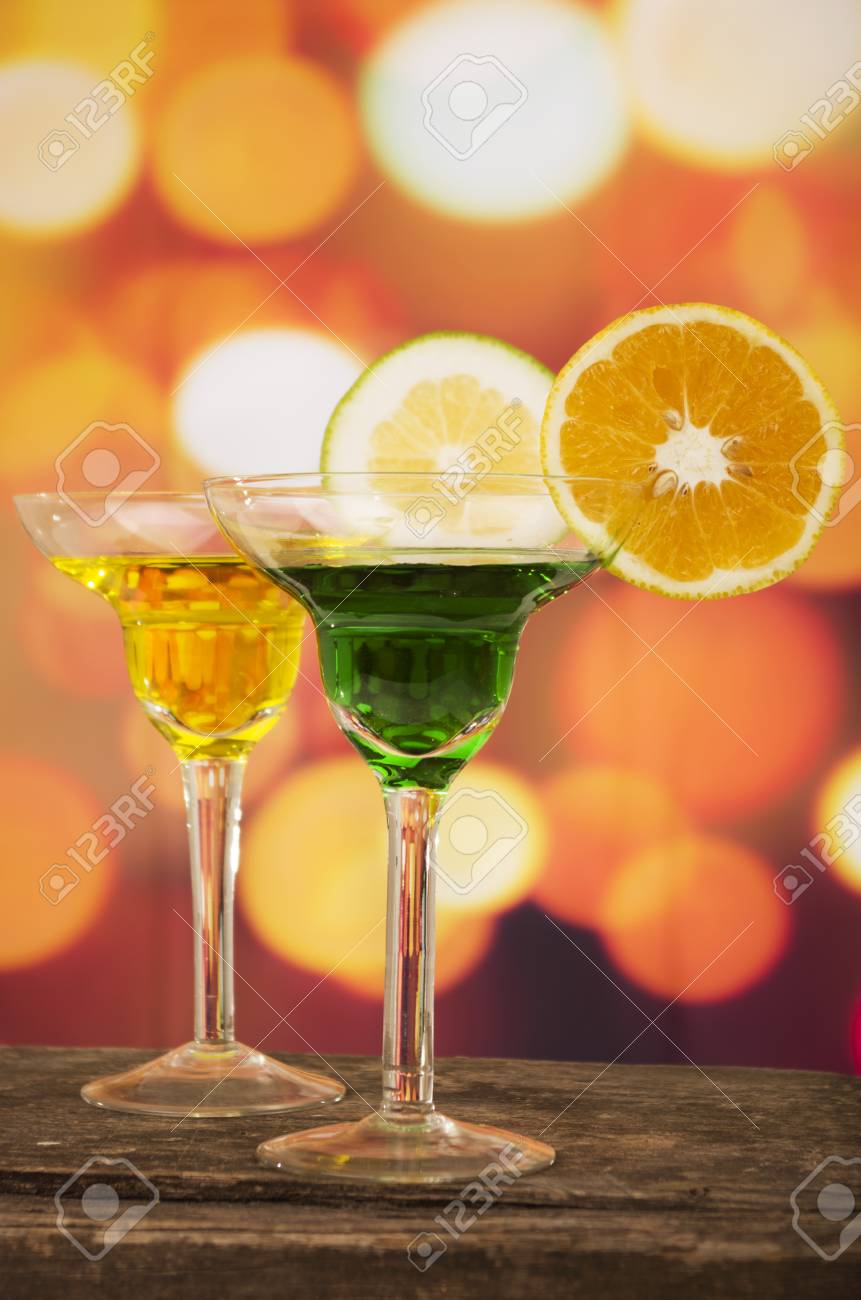 Green And Yellow Cocktails With Lime Slice Decoration On A Wooden