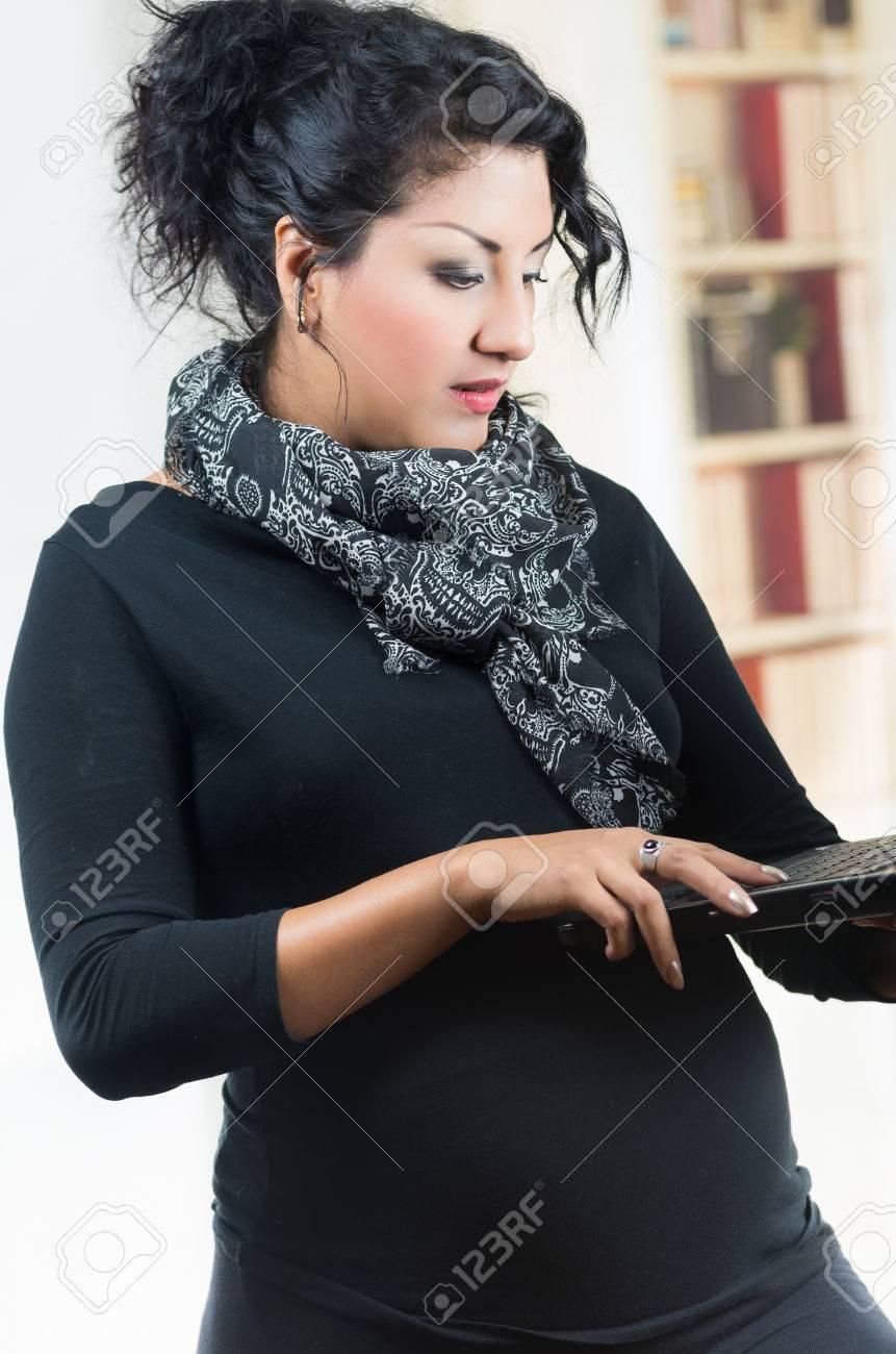 547adfcfd Foto de archivo - Mujer embarazada con ropa casual de pie sosteniendo la  computadora portátil
