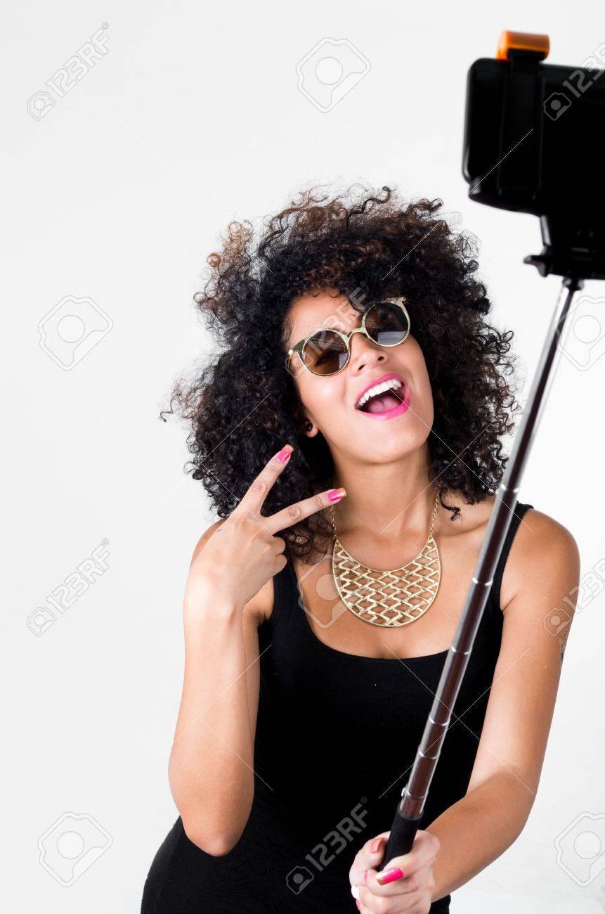 Modelo Hispánico Con Un Vestido Negro Atractivo Pelo Rizado Salvaje El Collar De Oro Y Gafas De Sol Posando Para Autofoto Utilizando Palo Para