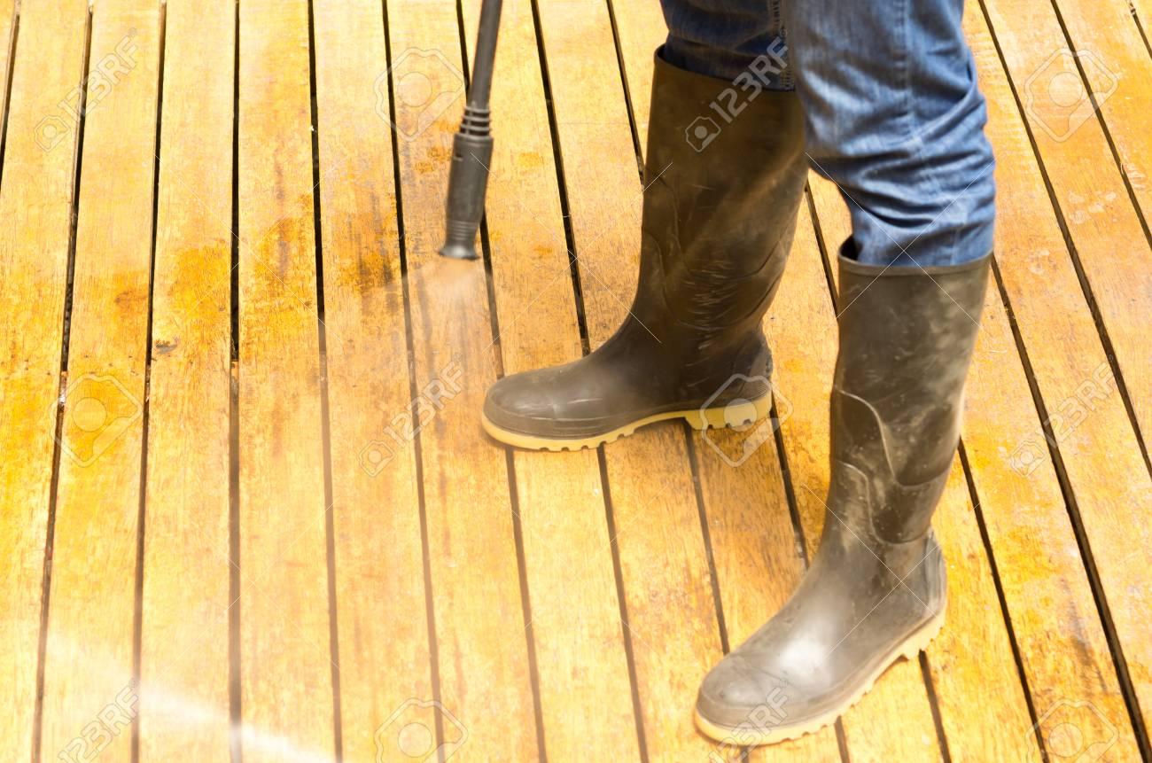 selección premium b62ee 2b605 El hombre que llevaba botas de goma utilizando limpiador alta presión de  agua en la superficie de madera terraza.