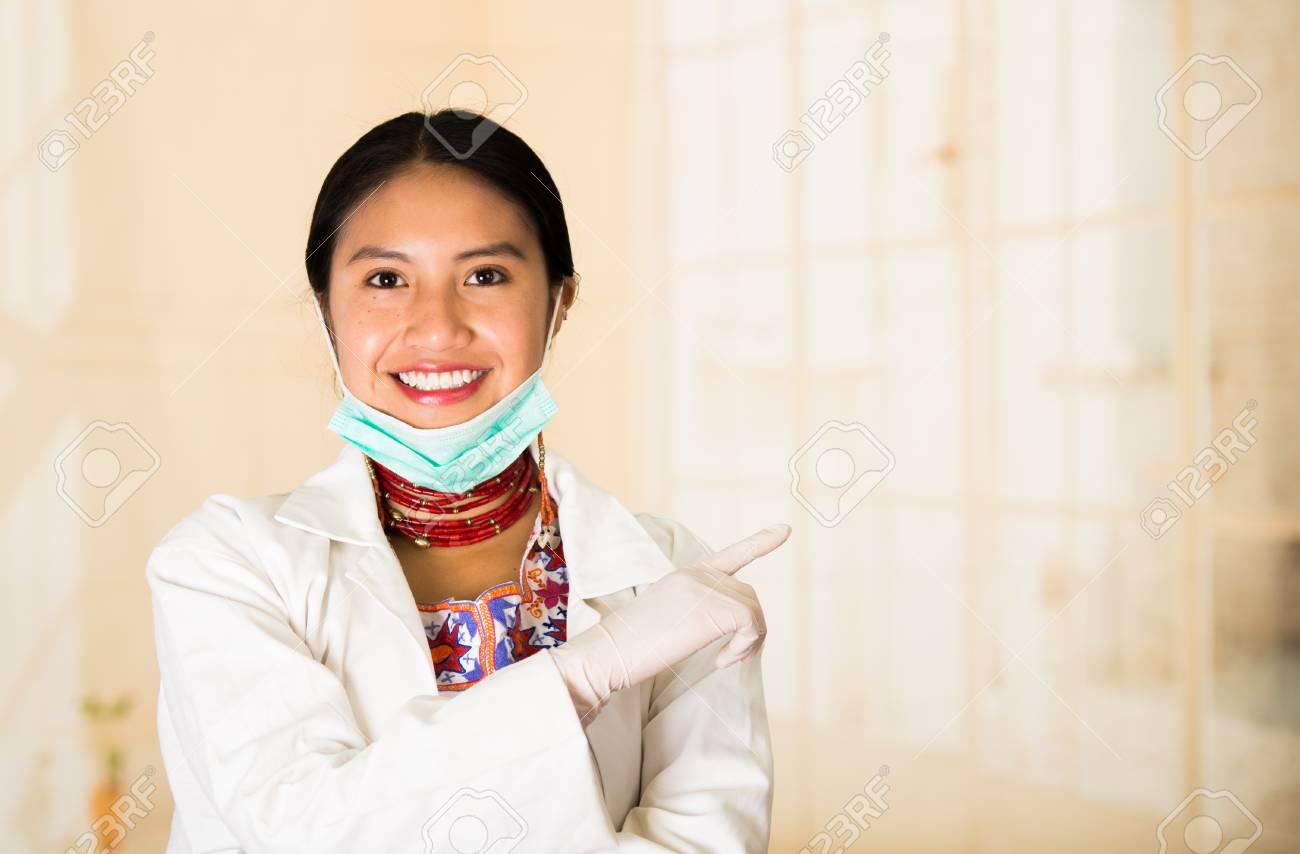 La giovane bella donna si è vestita in cappotto di medici e la collana rossa, maschera facciale tirata giù al mento, sorridendo felicemente, fondo