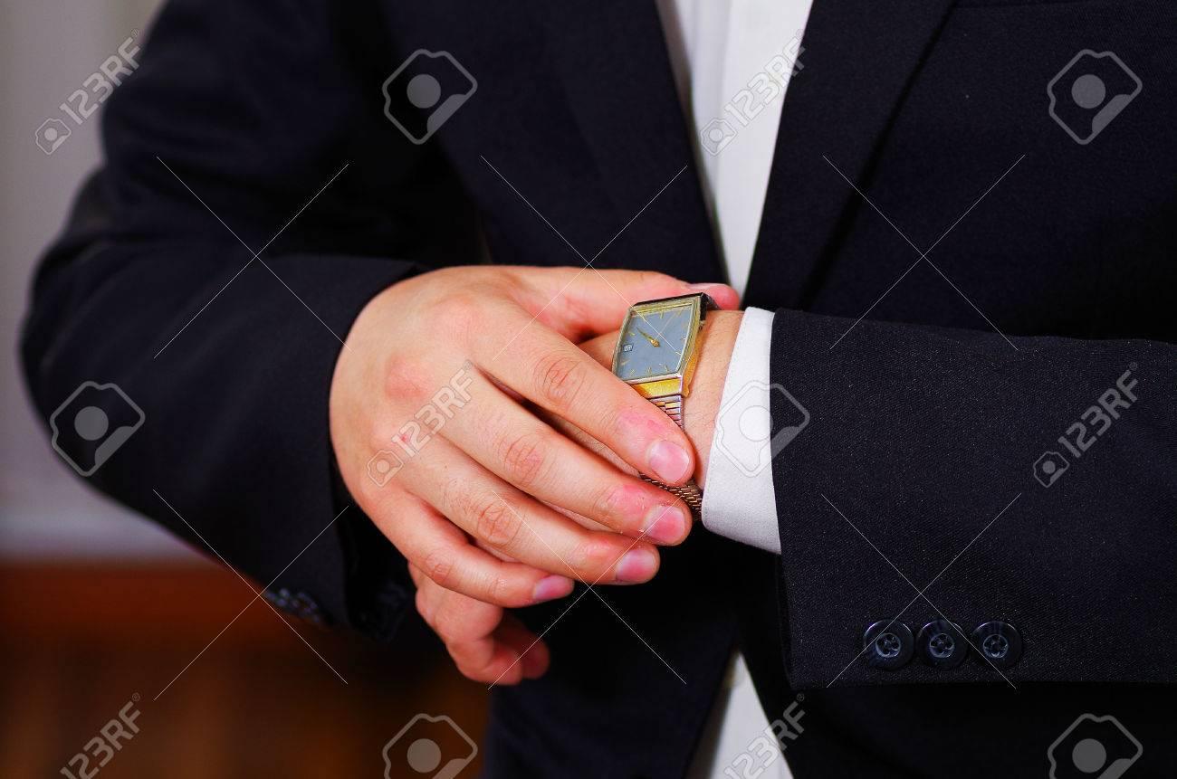 El uso de traje, el ajuste de reloj de pulsera de plata usando las manos, los brazos de los hombres del hombre del primer concepto de conseguir