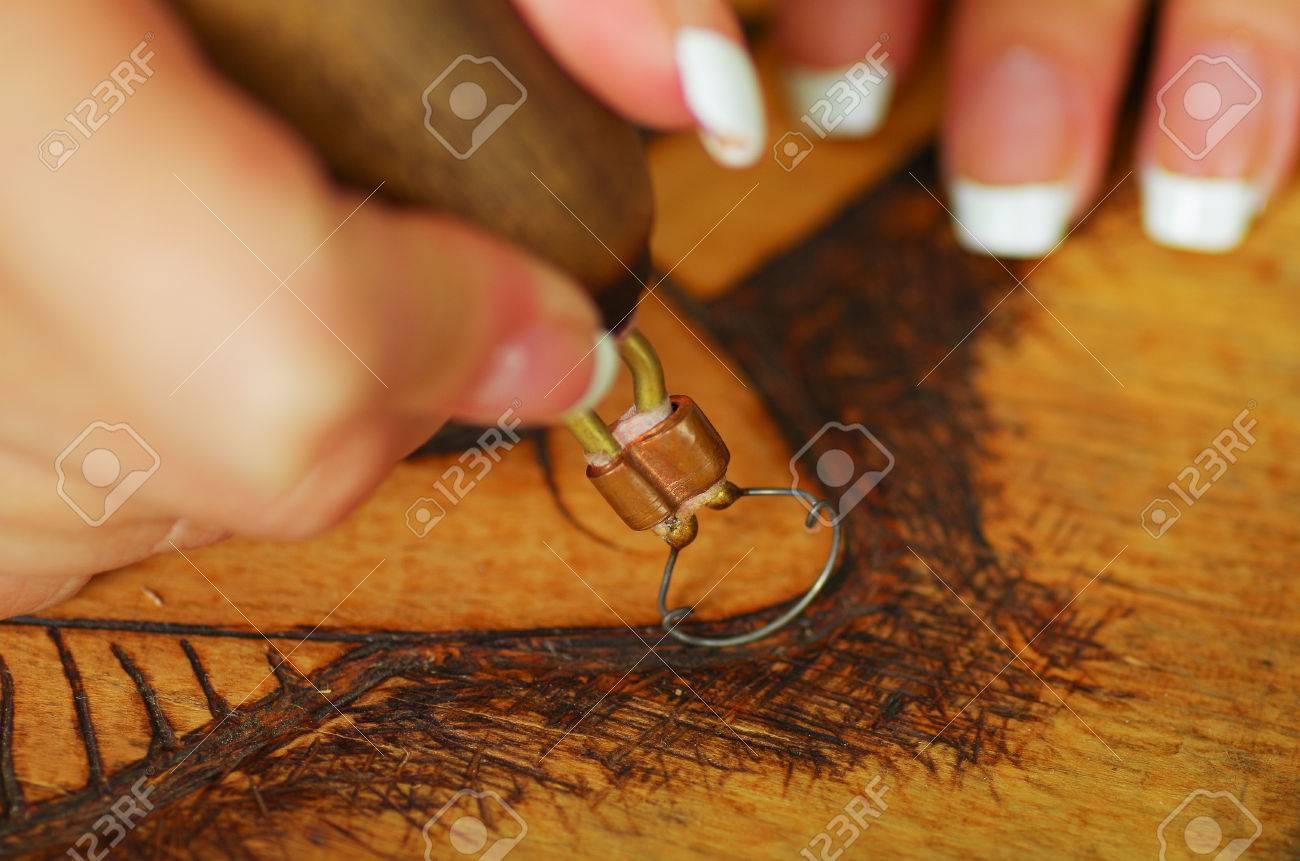 close up schuss von händen holz brennen mit pyrographie stift