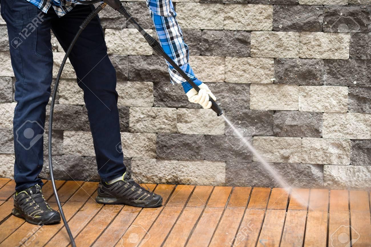 Cerca De Un Hombre De Limpieza De La Terraza Con Una Lavadora De Potencia Limpiador De Alta Presión De Agua Sobre La Superficie De La Terraza De