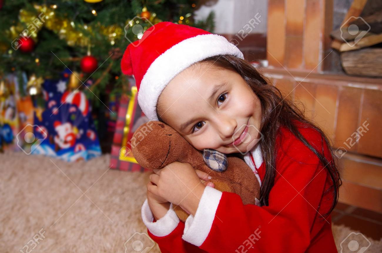 Beautiful Smiling Litle Girl Wearing A Christmas Clothes Hugging Moose Teddy With