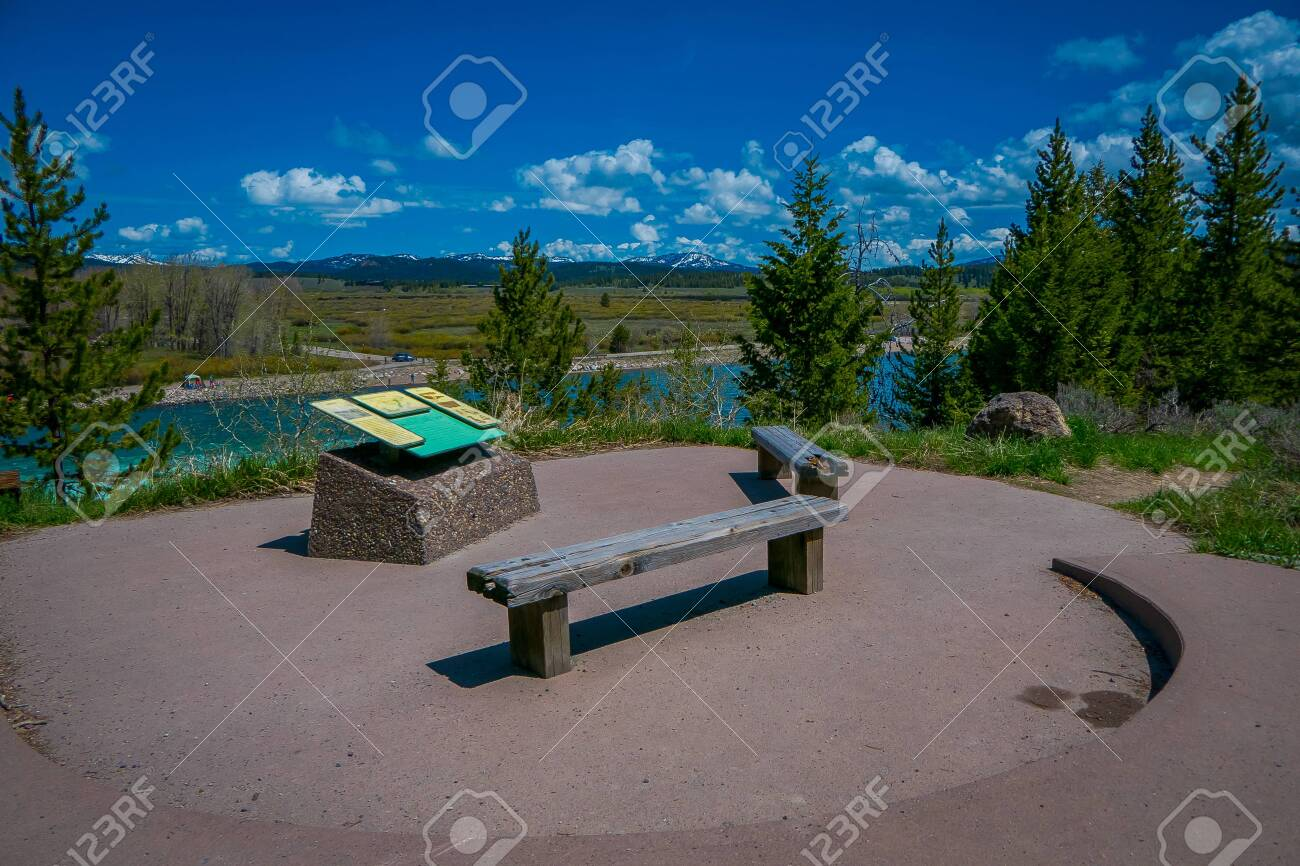 YELLOWSTONE, MONTANA, USA MAY 24, 2018: Beautiful outdoor view of informative sign and wooden public chair with a view of Jackson Lake Dam in Grand Teton National Park - 120296000