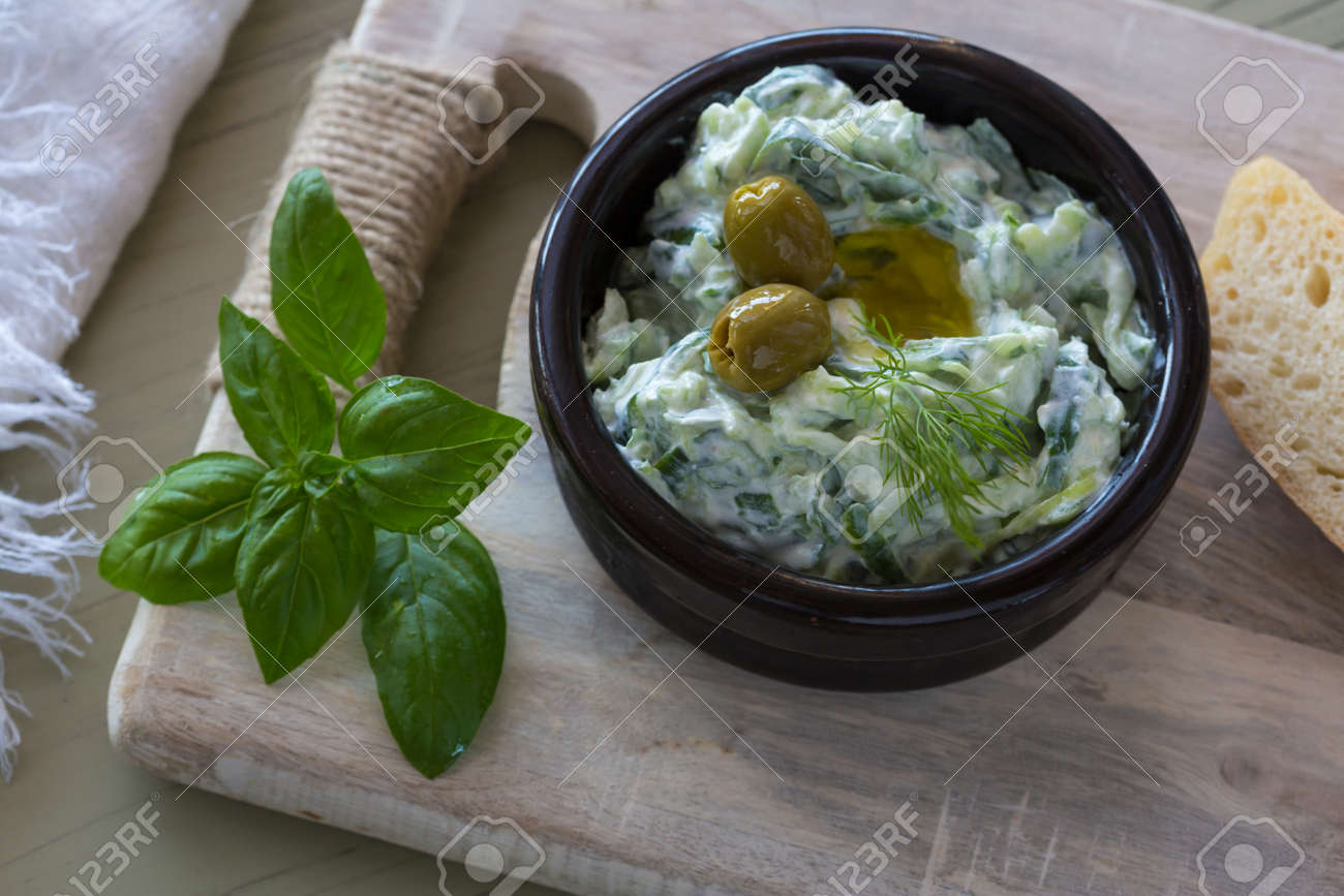 Greek dip sauce or dressing tzatziki and ingredients decorated with olive oil and basil on wooden table. - 150727569