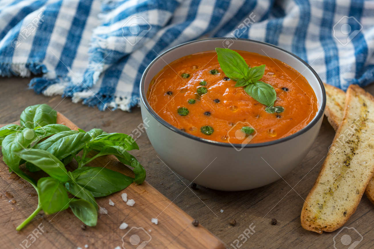 A bowl of fresh tomato soup in white ceramic bowl, garnished with basil, croutons, seasoning and a drizzle of olive oil, and served with crusty bread - 150727499