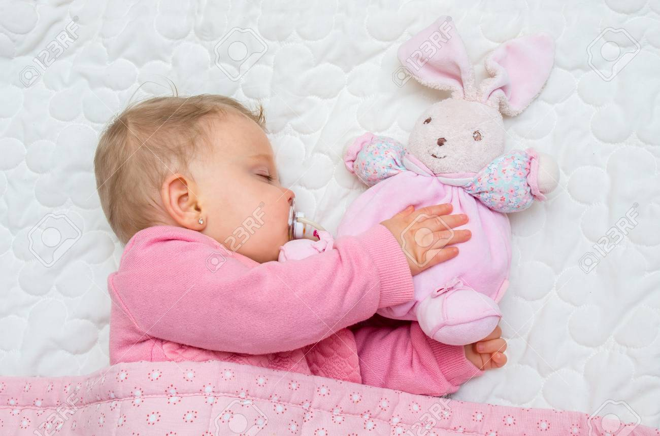 b4b74c17c Infant Baby Girl Sleeping On Bed With His Toy Bunny Stock Photo ...