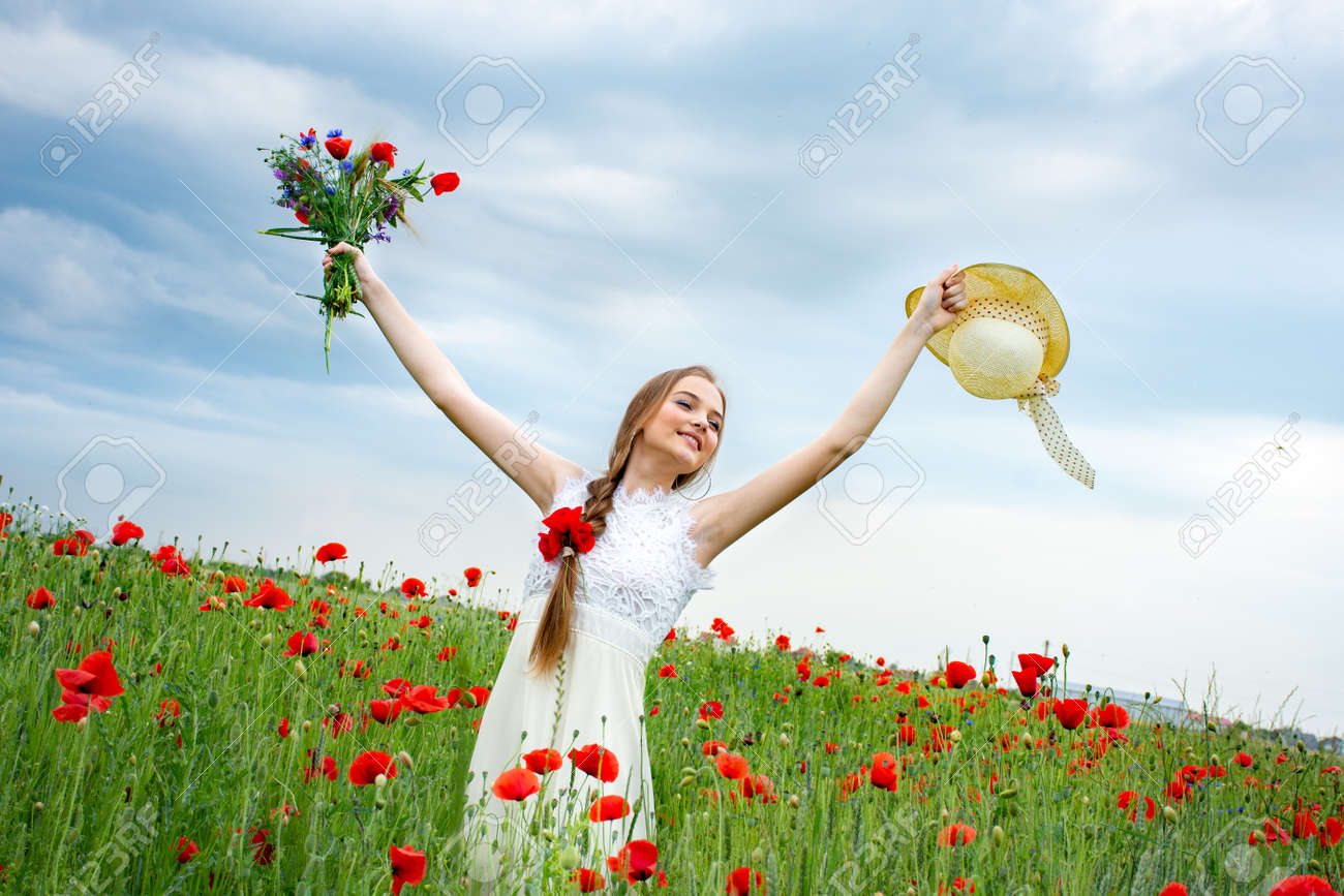 teenage girl standing in a field with wild poppies in a hat looking into the distance - 156915107