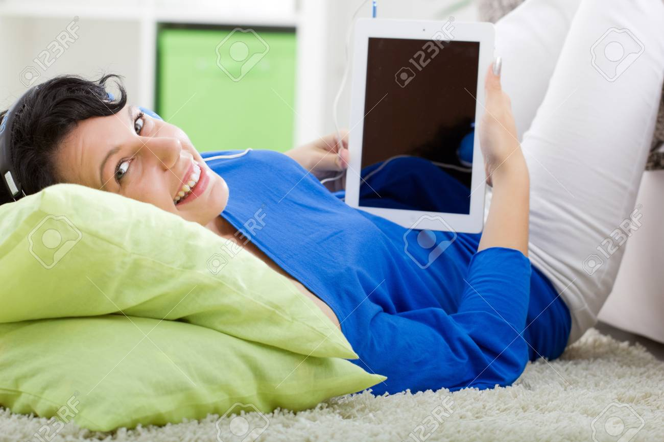Young modern woman laying in sofa with electronic tablet and headphones at home Stock Photo - 20685164