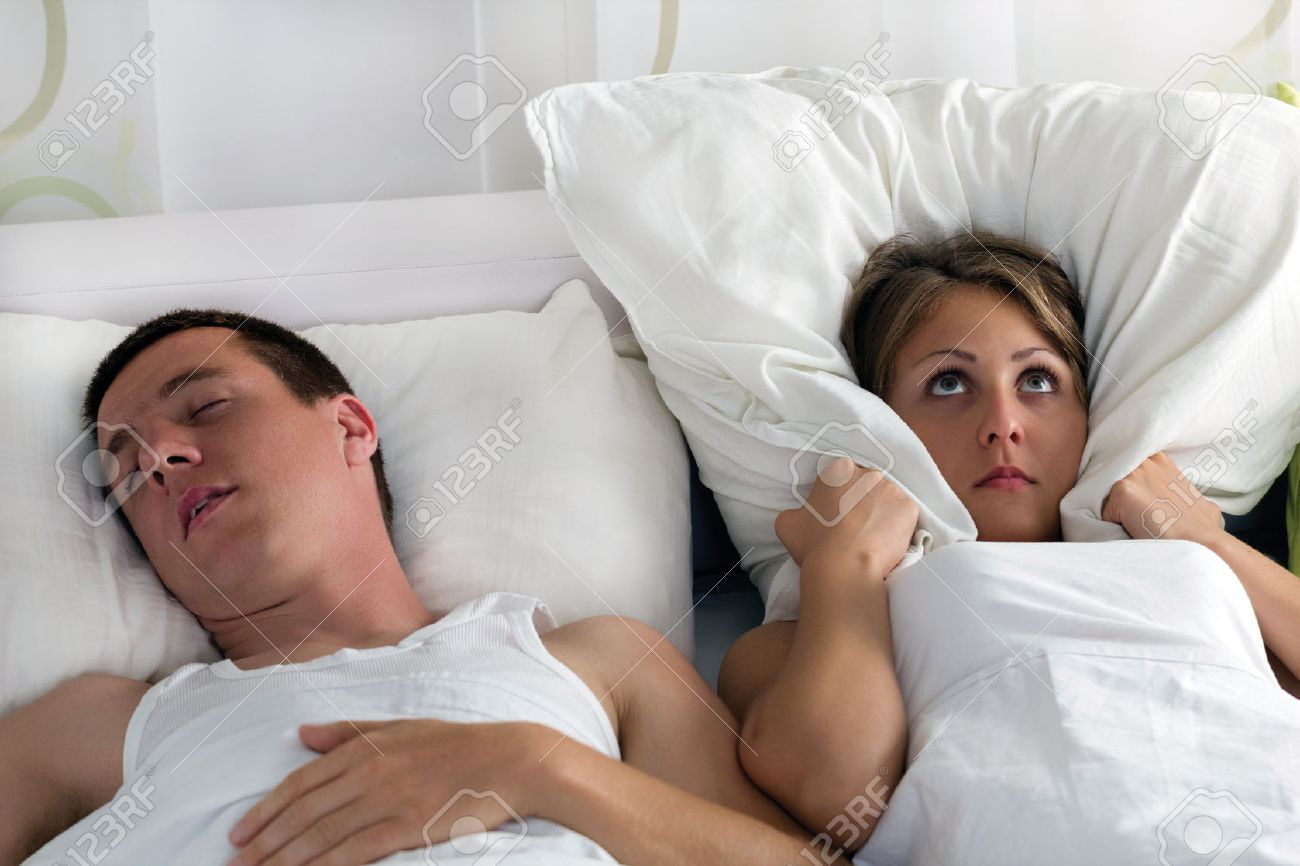 Snoring man and young woman, couple sleeping in bed - 22742715