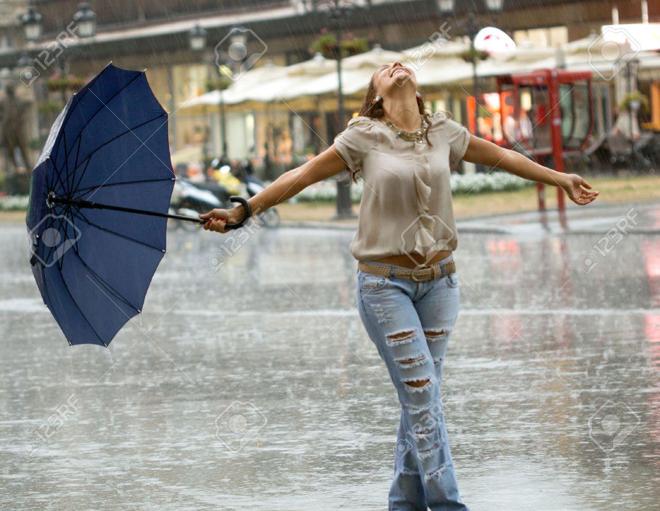 smiling woman with umbrella enjoying in the rain - 22742785