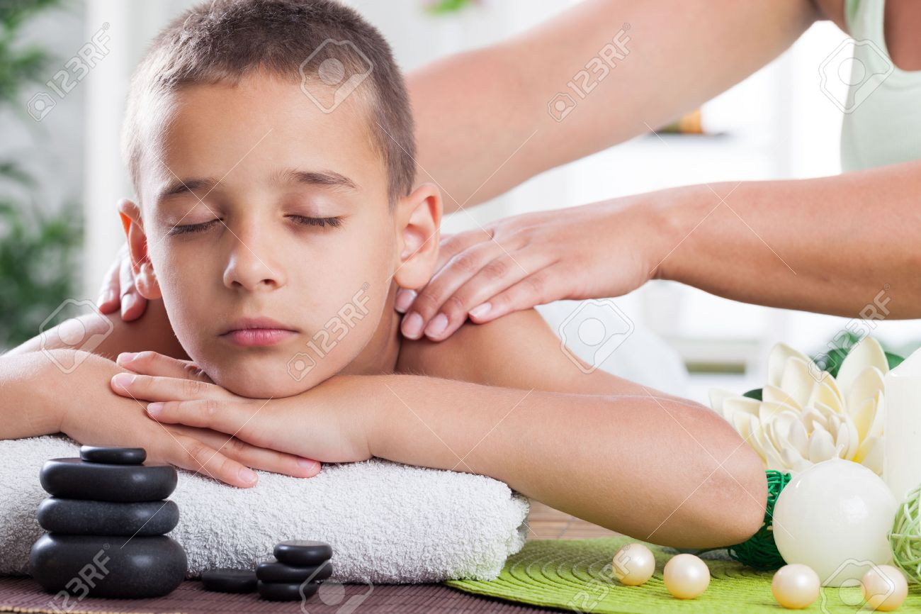young boy relaxing in spa. stone massage. - 22934008