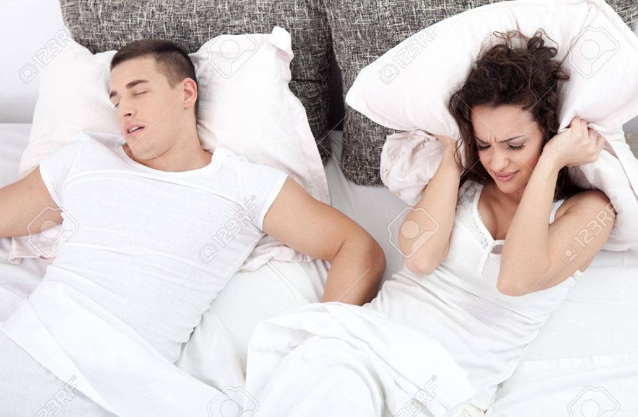 Young couple in bed woman trying to sleep while a man is snoring - 27660566