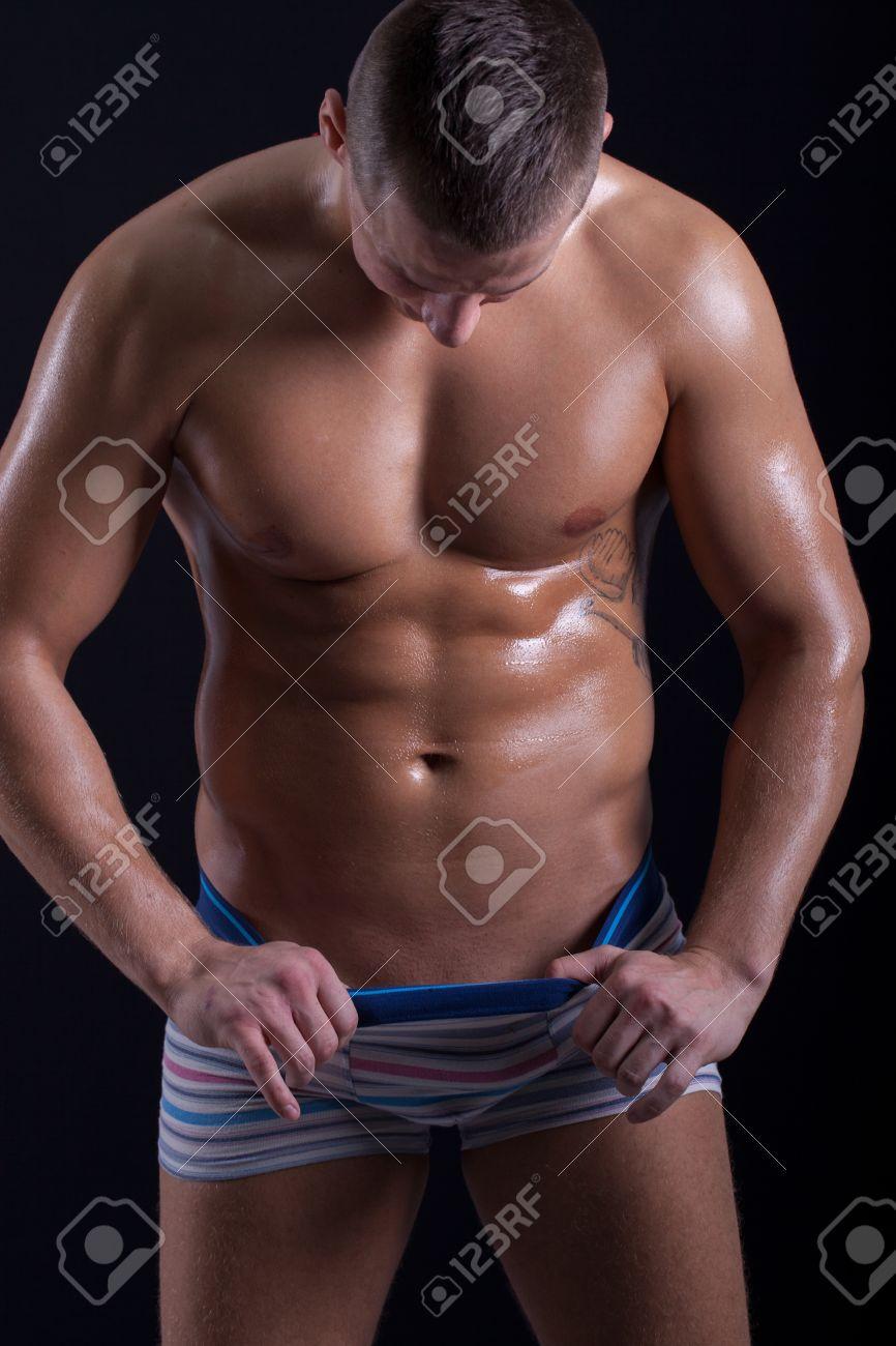 homme musclé regardant vers le bas dans son pantalon Banque d'images - 28703523