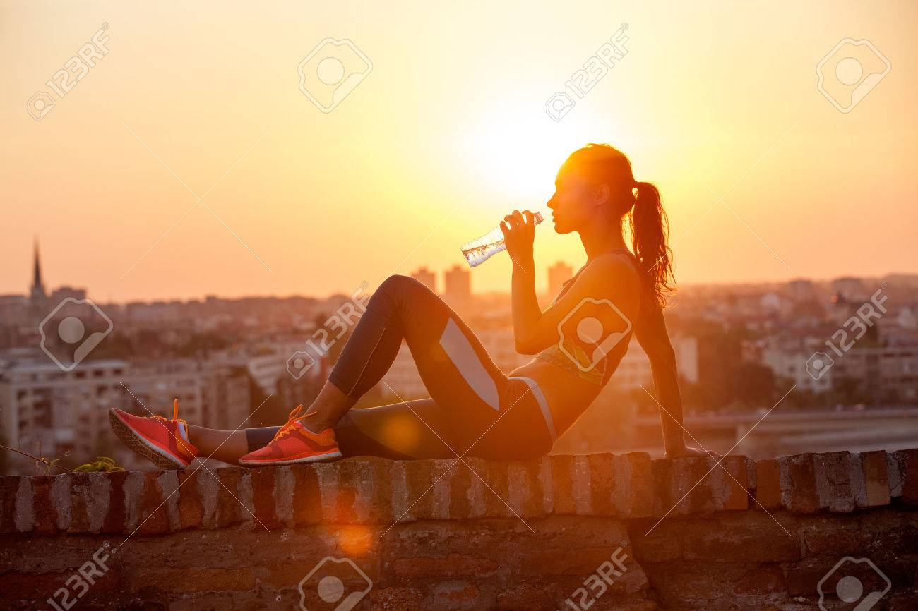 silhouette of girl drinking water outdoor - 29259294