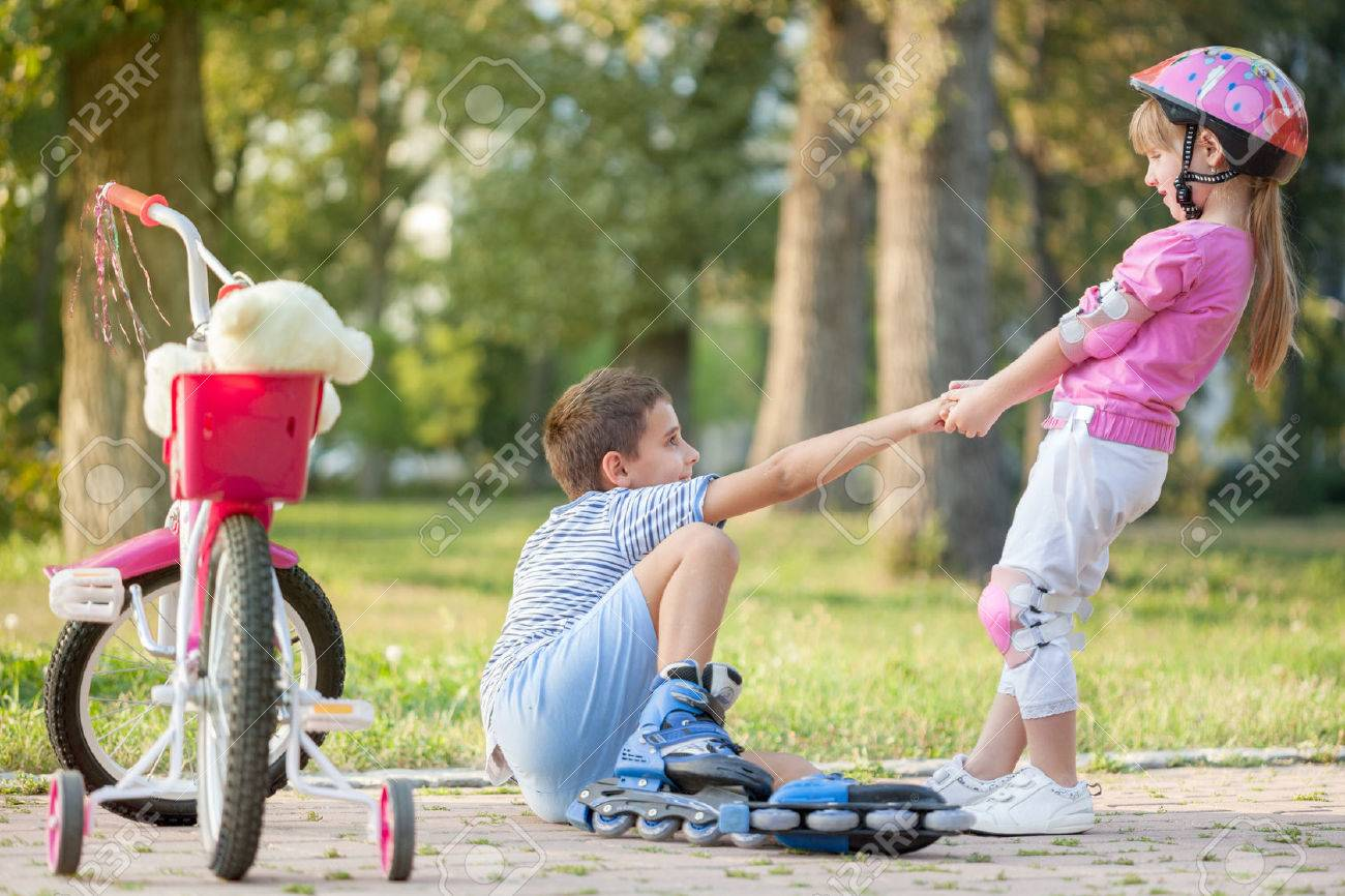 girl in park, helps boy with roller skates to stand up - 31526296