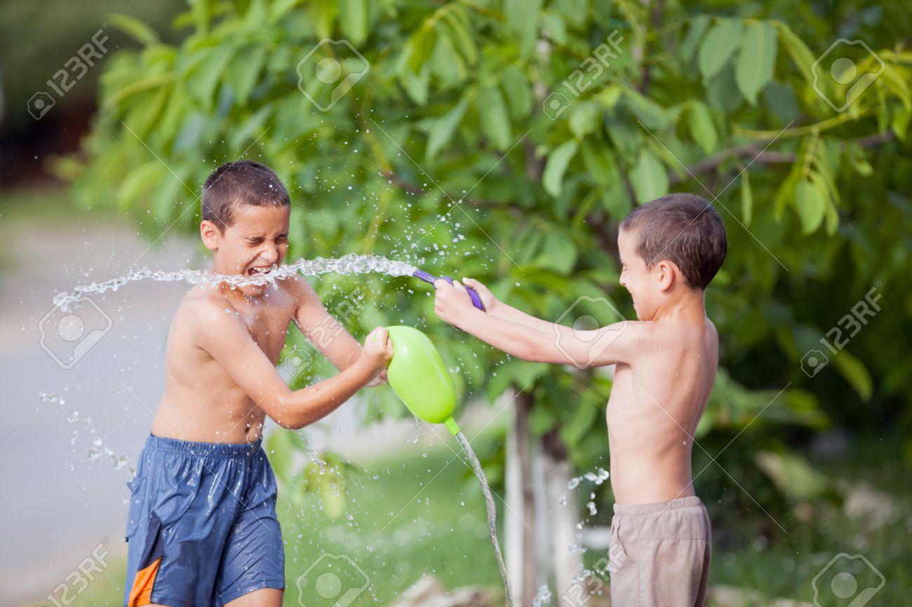 Juego De Dos Muchachos Y Se Rocian Con Agua En Un Parque O Patio De