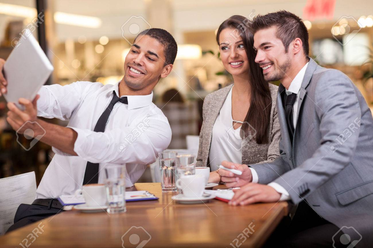 Three successful business people taking a happy Selfie in restaurant - 46088195