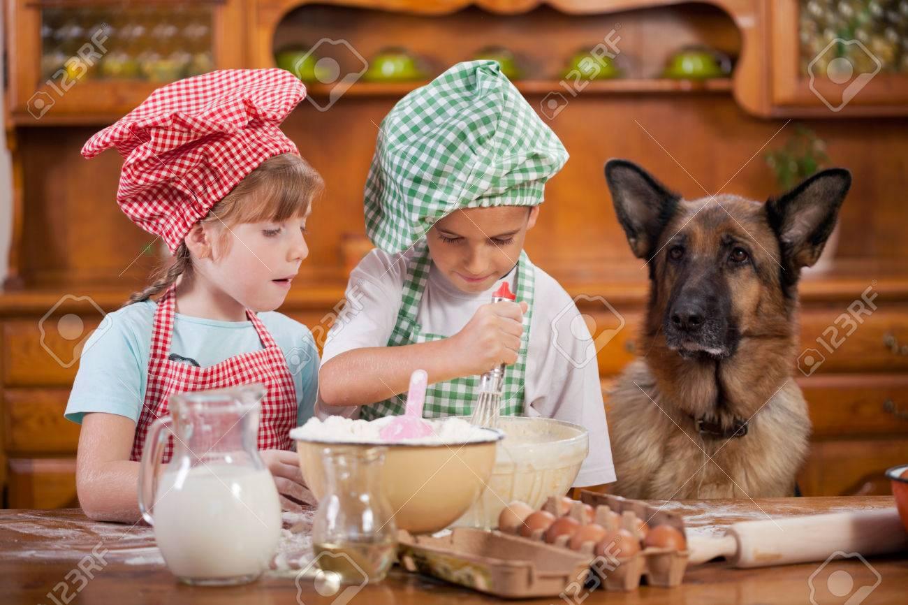 les enfants préparent des biscuits dans la cuisine, berger allemand regarder Banque d'images - 47233854