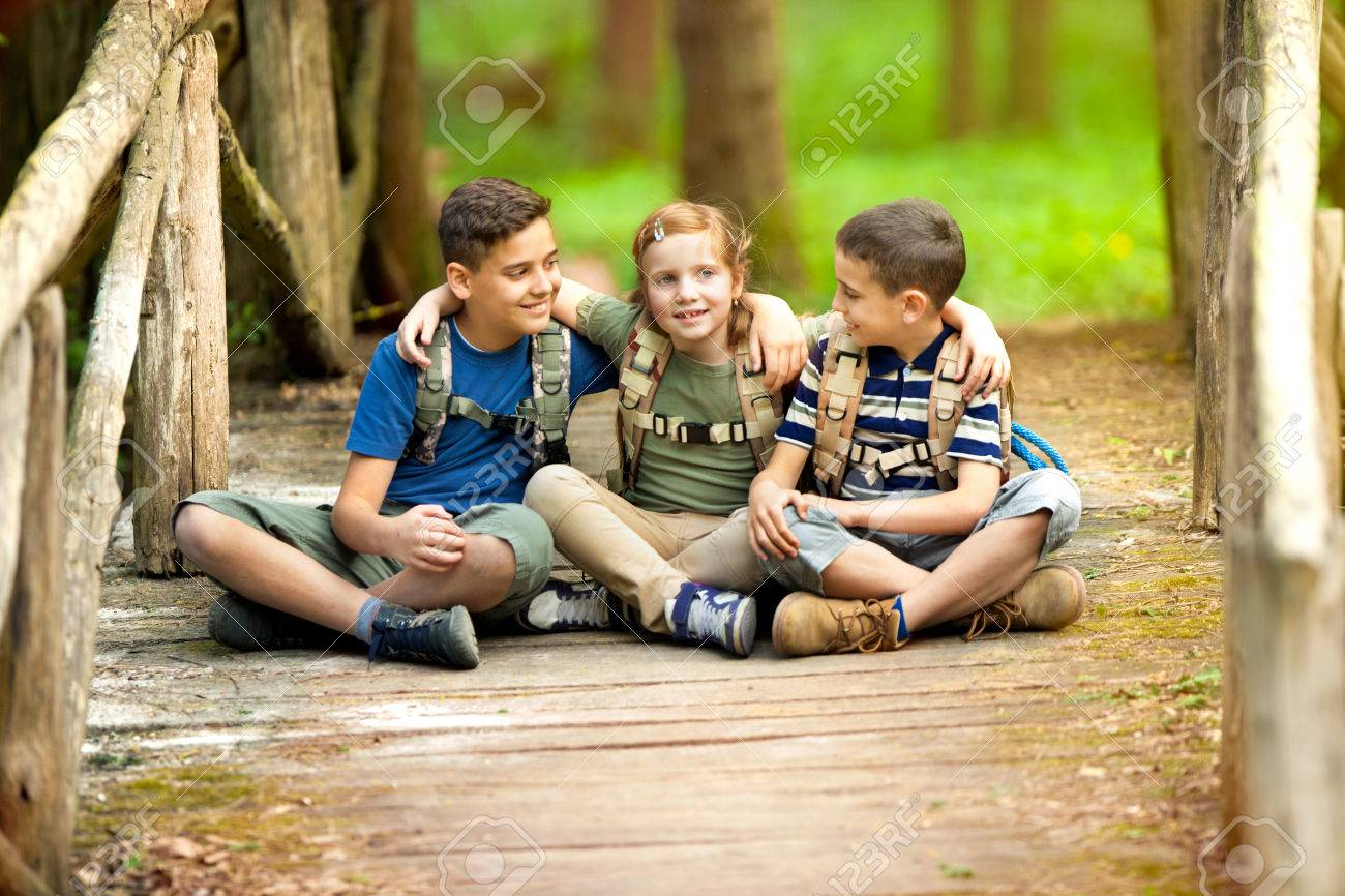 Young scouts sitting on old wooden bridge in the woods - 76070560