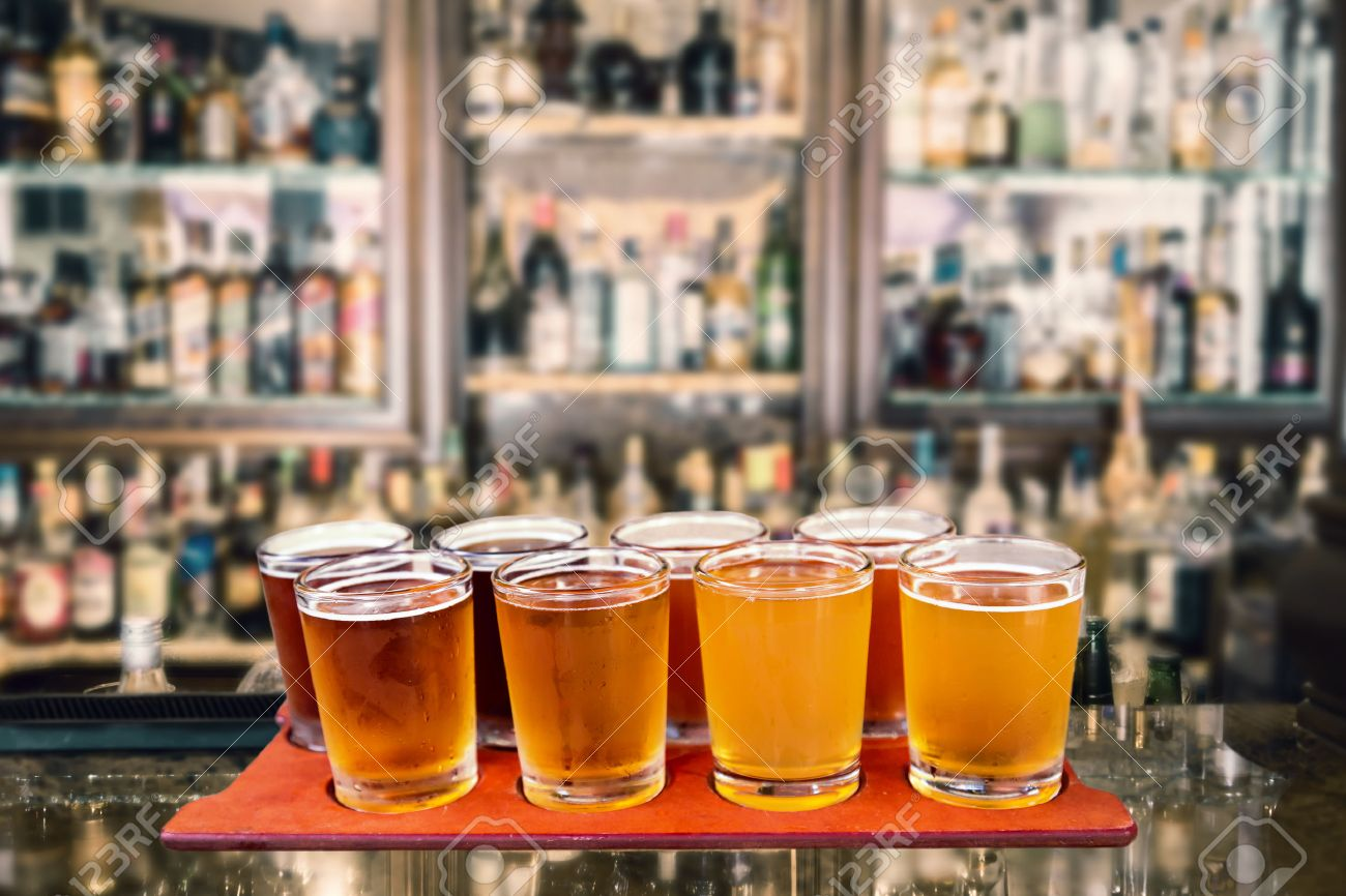 beer flight of eight sampling glasses of craft beer on a serving board in a bar