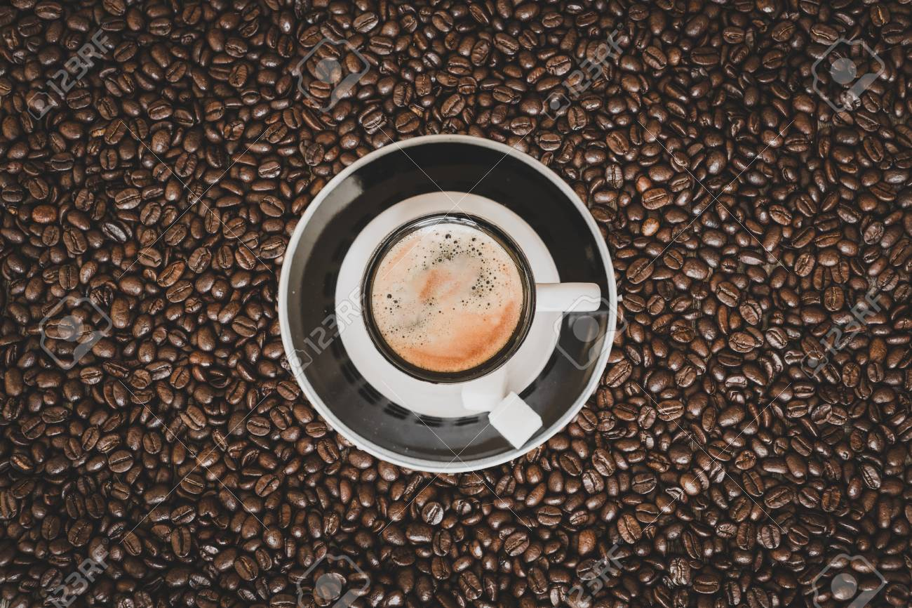 Single small espresso coffee cup on roasted coffee beans background - 97251853