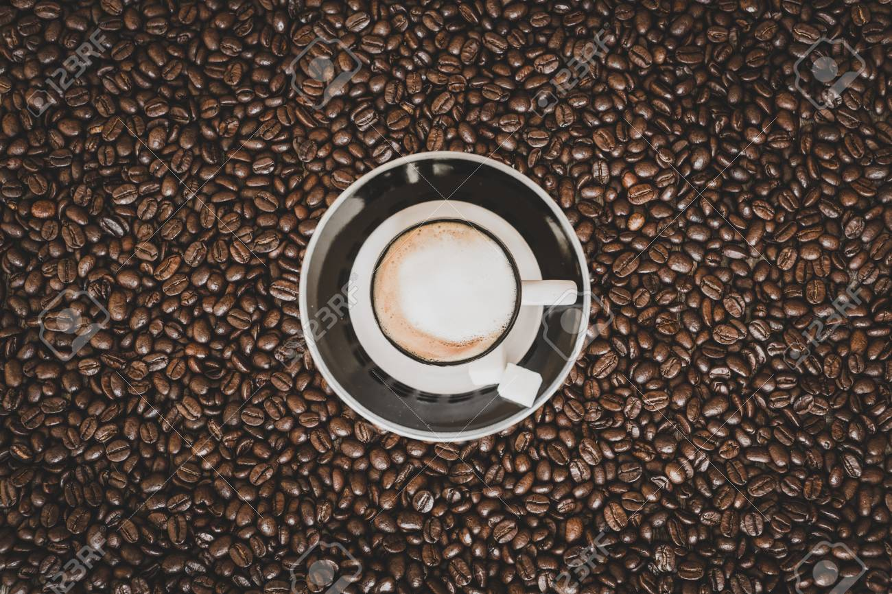 Single small espresso coffee cup on roasted coffee beans background - 97294497
