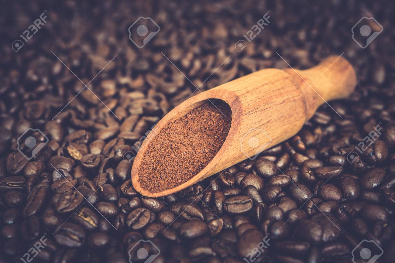 Wooden scoop with ground coffee on roasted coffee beans background - 97294498