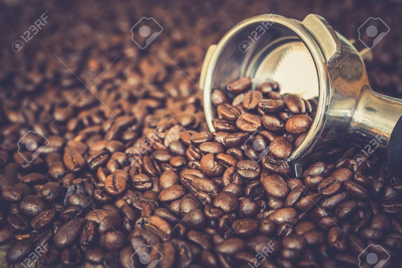 Metal espresso machine scoop on roasted coffee beans background - 97251851