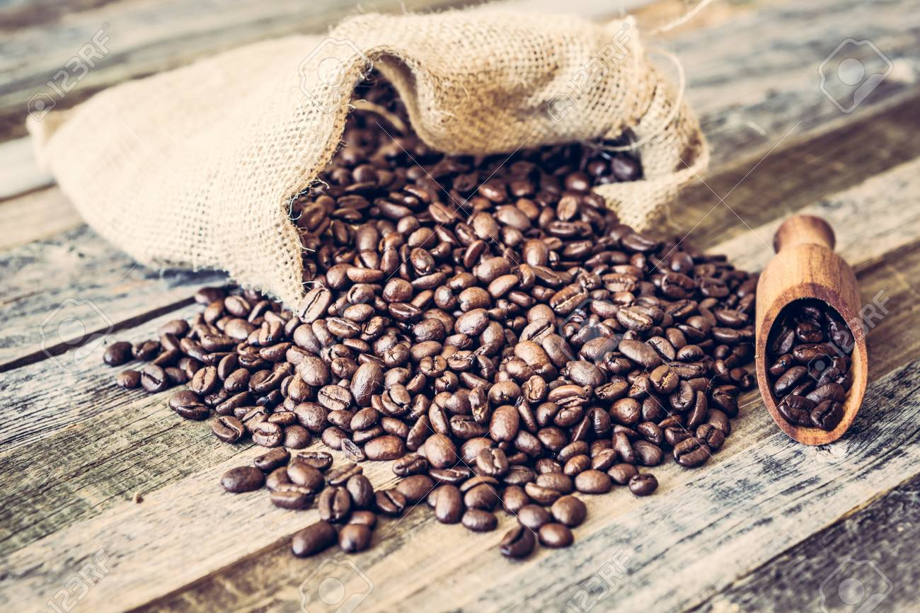 Roasted coffee beans in a burlap bag on wooden table background - 97275873