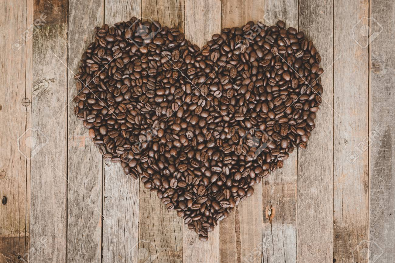 Roasted coffee beans in a shape of heart on wooden background - 97291319