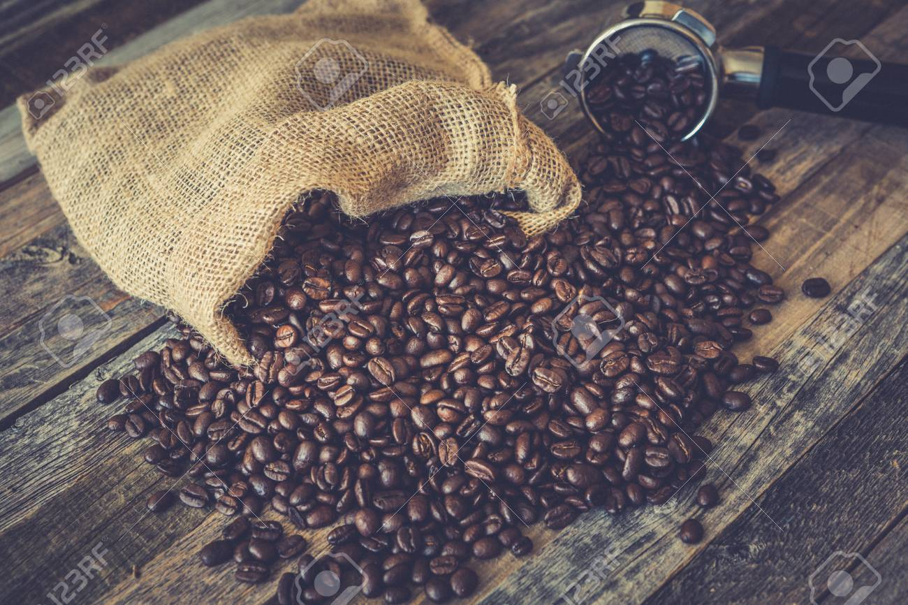 Roasted coffee beans in a burlap bag on wooden table background with espresso machine scoop - 97288245