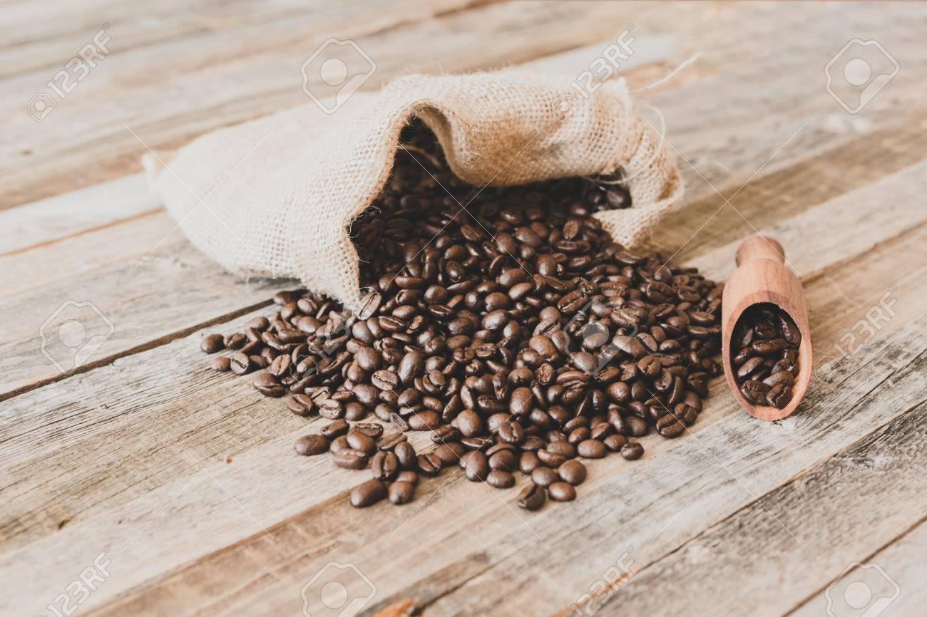 Roasted coffee beans in a burlap bag on wooden table background - 97294225