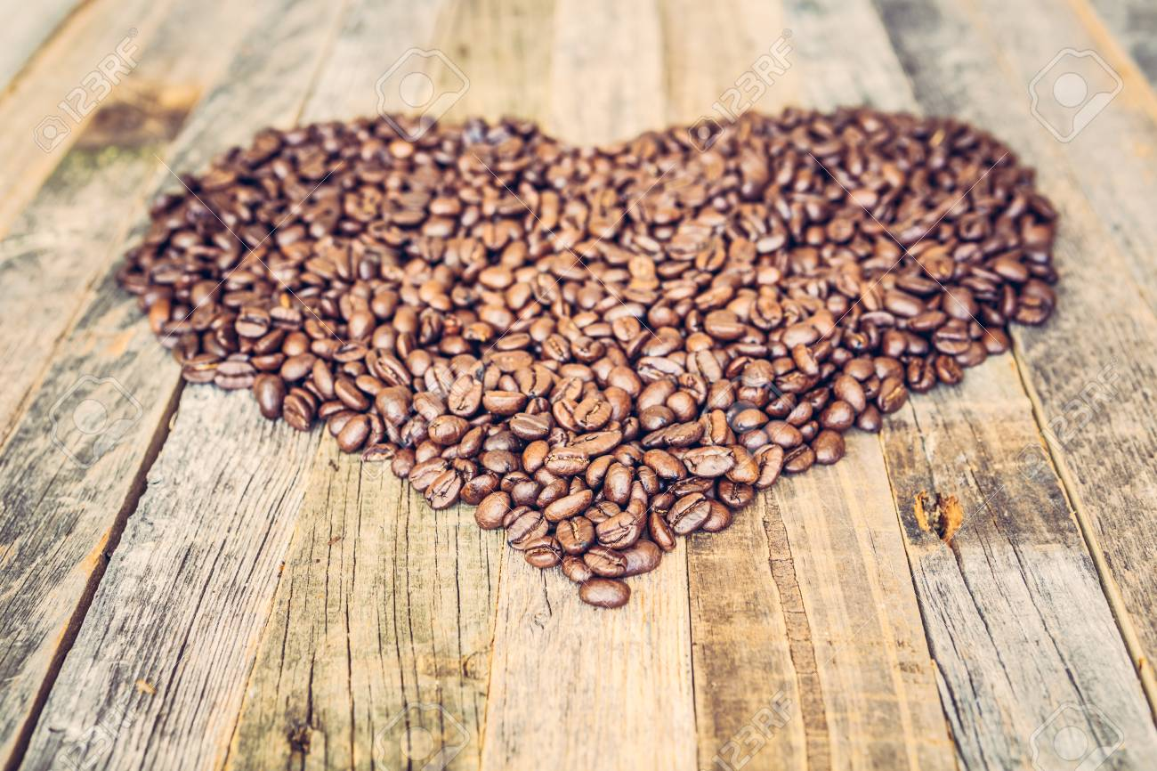 Roasted coffee beans in a shape of heart on wooden background - 97271328