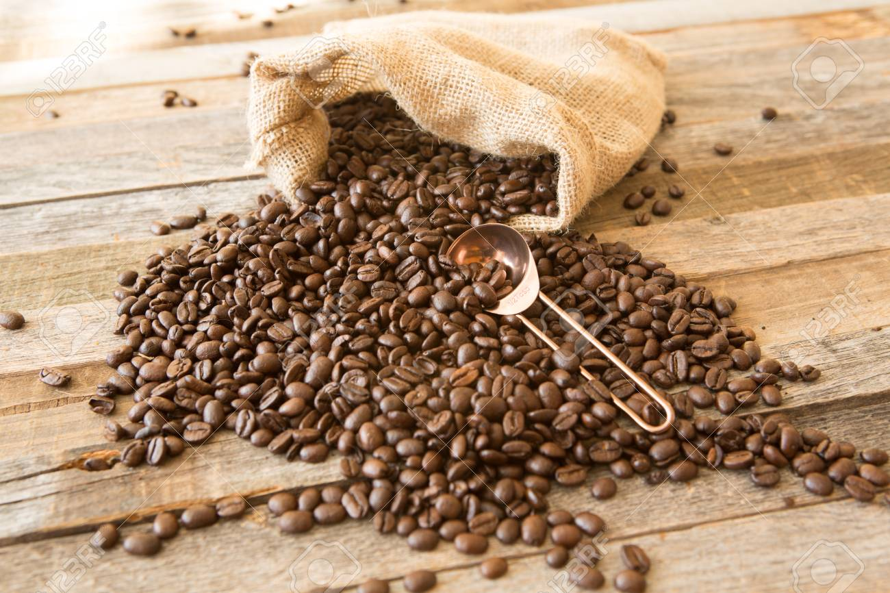 Roasted coffee beans in a burlap bag on wooden table background with copper scoop - 97294254