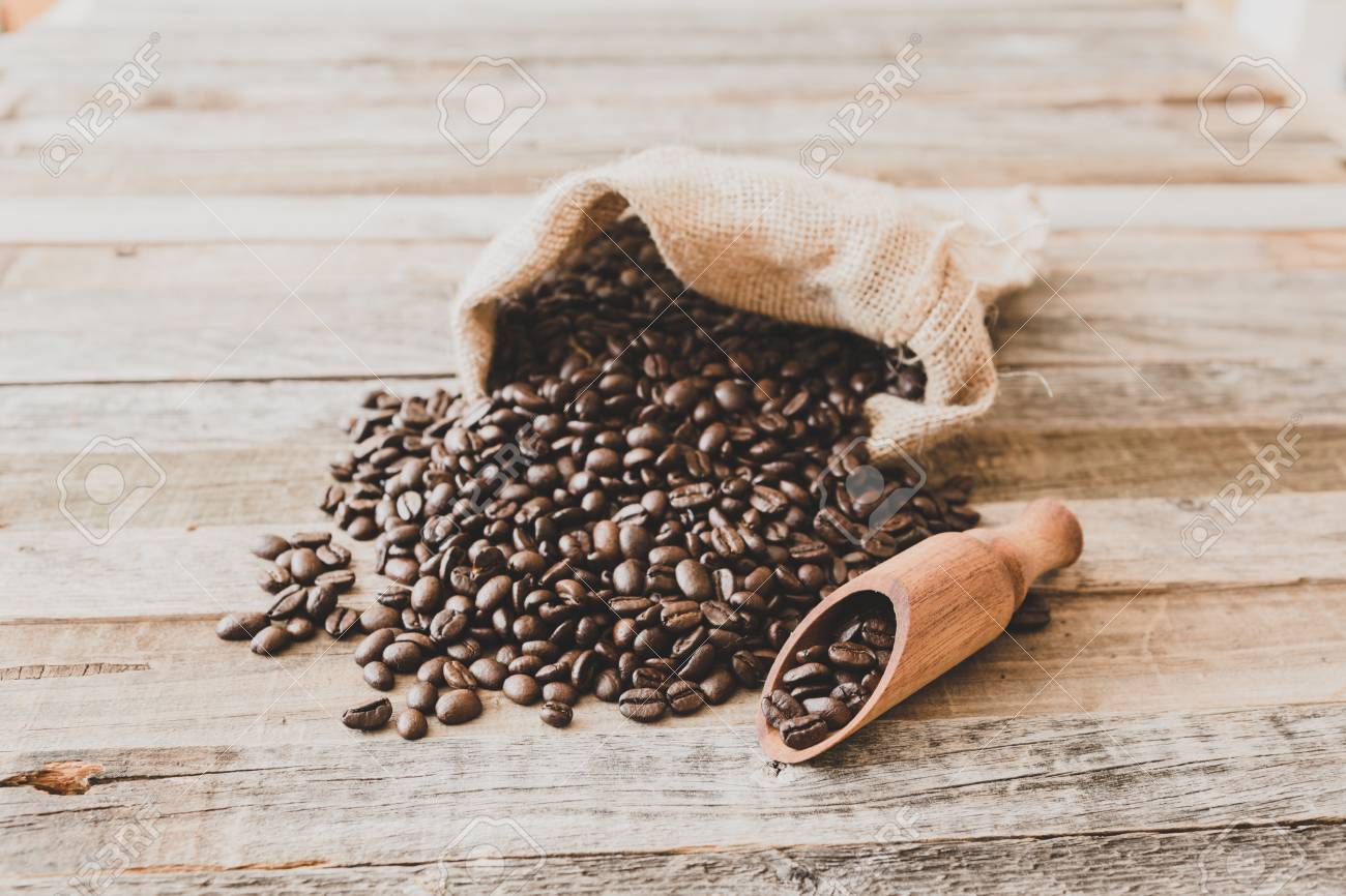 Roasted coffee beans in a burlap bag on wooden table background - 97291322