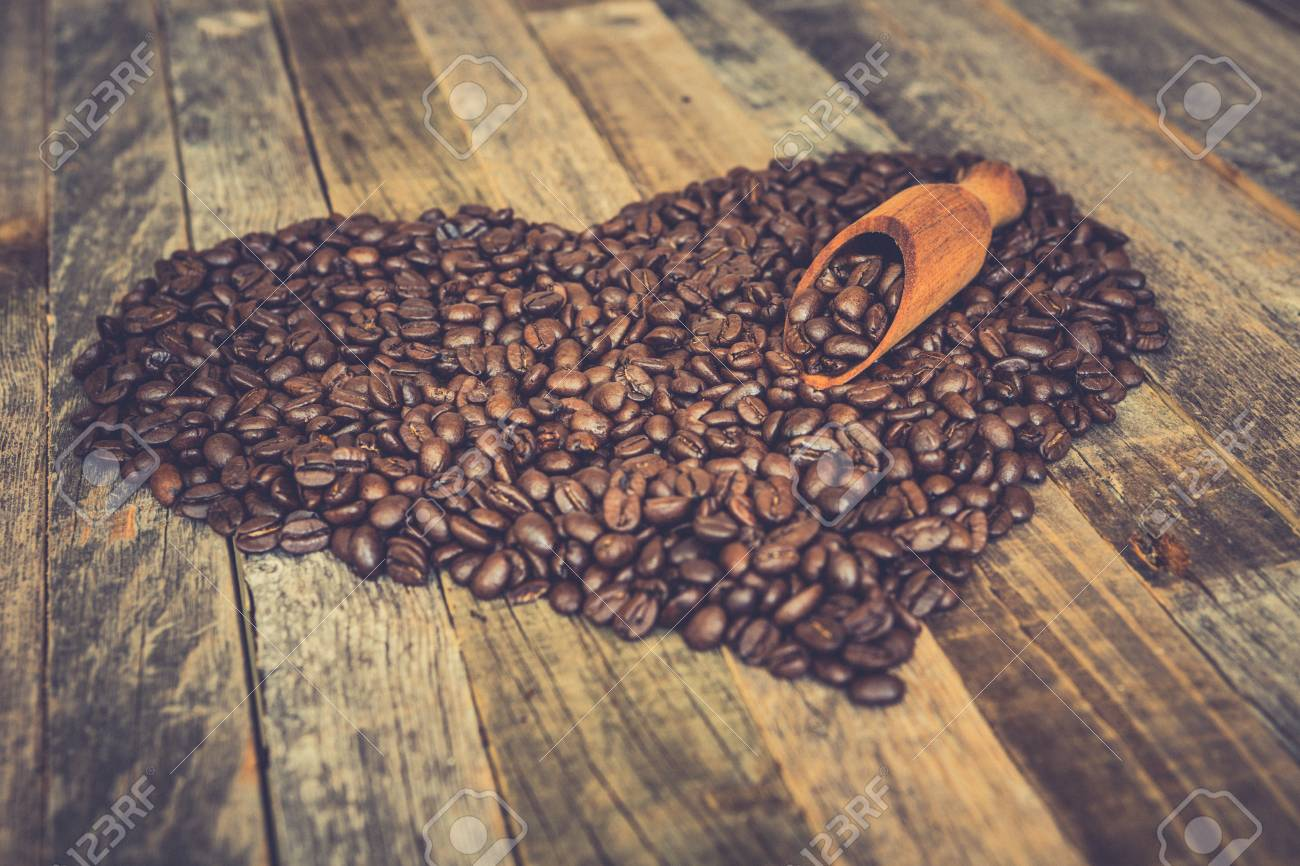 Roasted coffee beans in a shape of heart on wooden background - 97291326